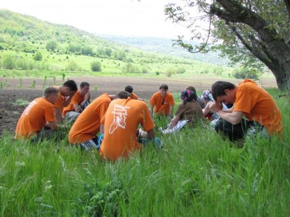 Binecuvântând prin rugăciune femeile aflate la muncă pe câmp